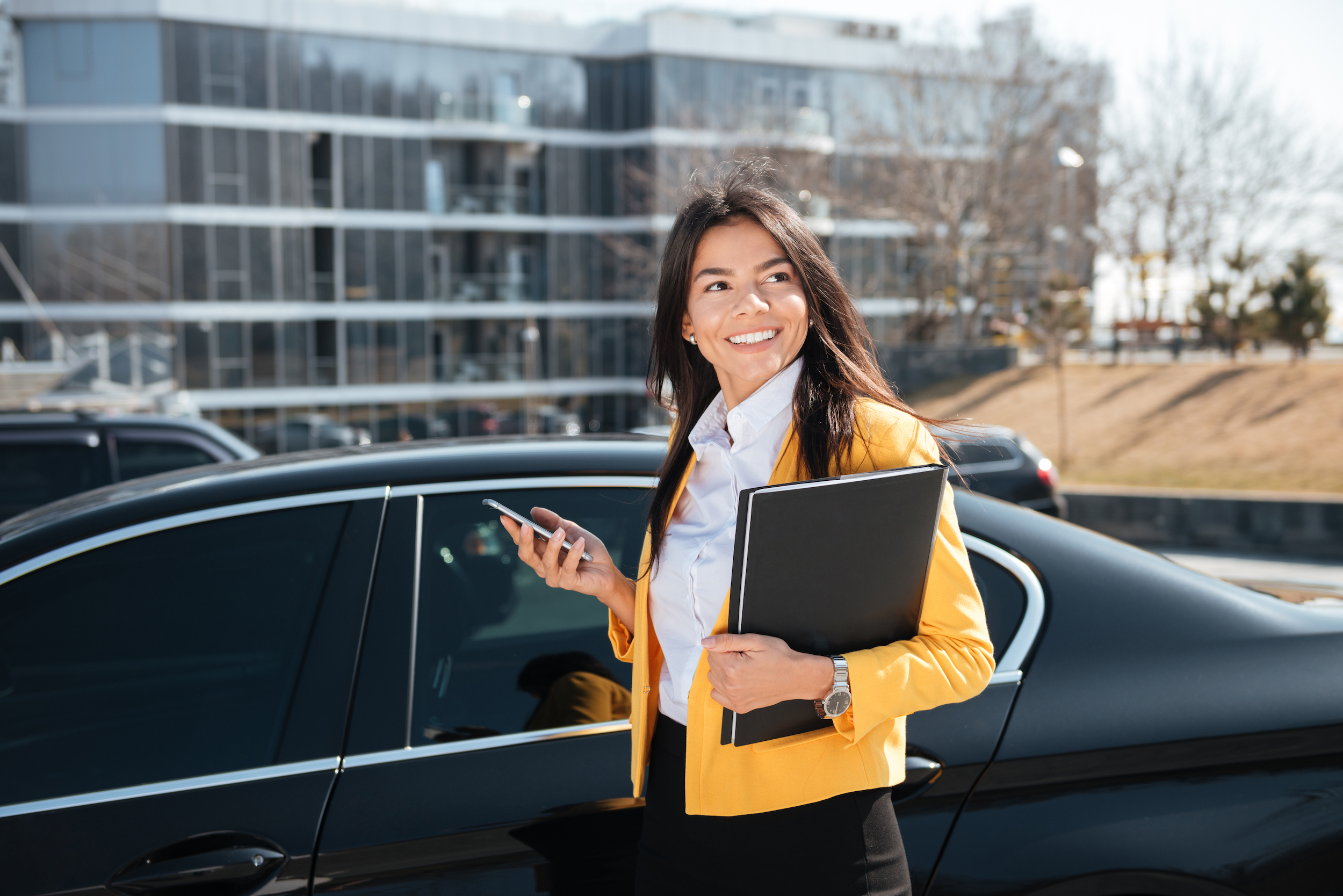 Happy young businesswoman in yellow jacket with folder standing near the car and using mobile phone