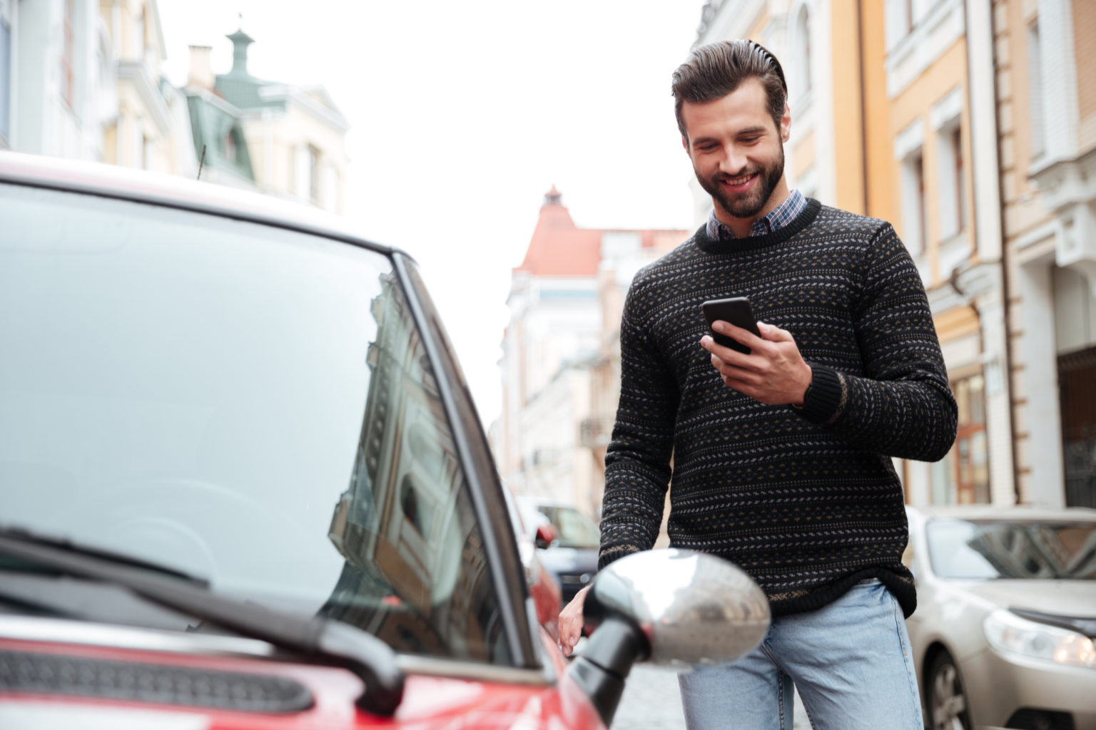 Portrait,Of,A,Satisfied,Young,Man,In,Sweater,Using,Mobile